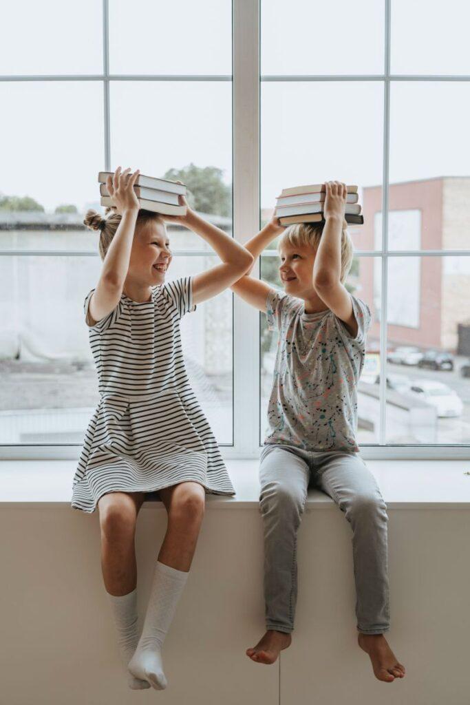 Copii asezati pe pervaz in sala de clasa de cursuri de engleza cu cartile pe cap zambesc