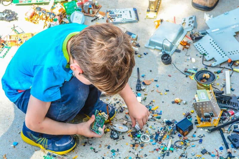 copil imbracat in albastru aplecat asupra a nenumarate fragmente dintr-un aparat care a fost stricat