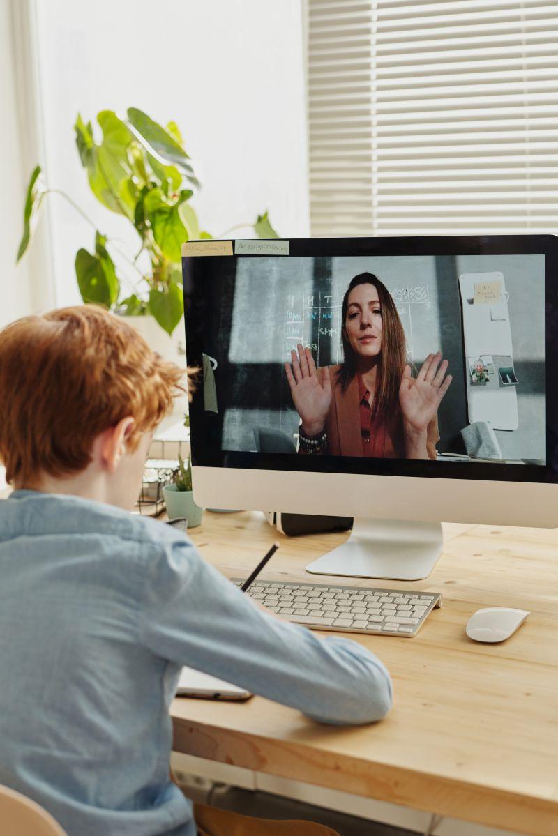 copil care face lectii online si comunica cu profesoara lui de limba engleza pe care o vede pe monitor