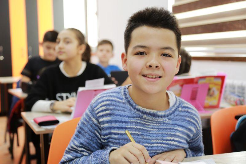 baietel imbracat in bluza cu dungi albastre in sala de clasa fericit ca se afla la scoala alaturi de colegi