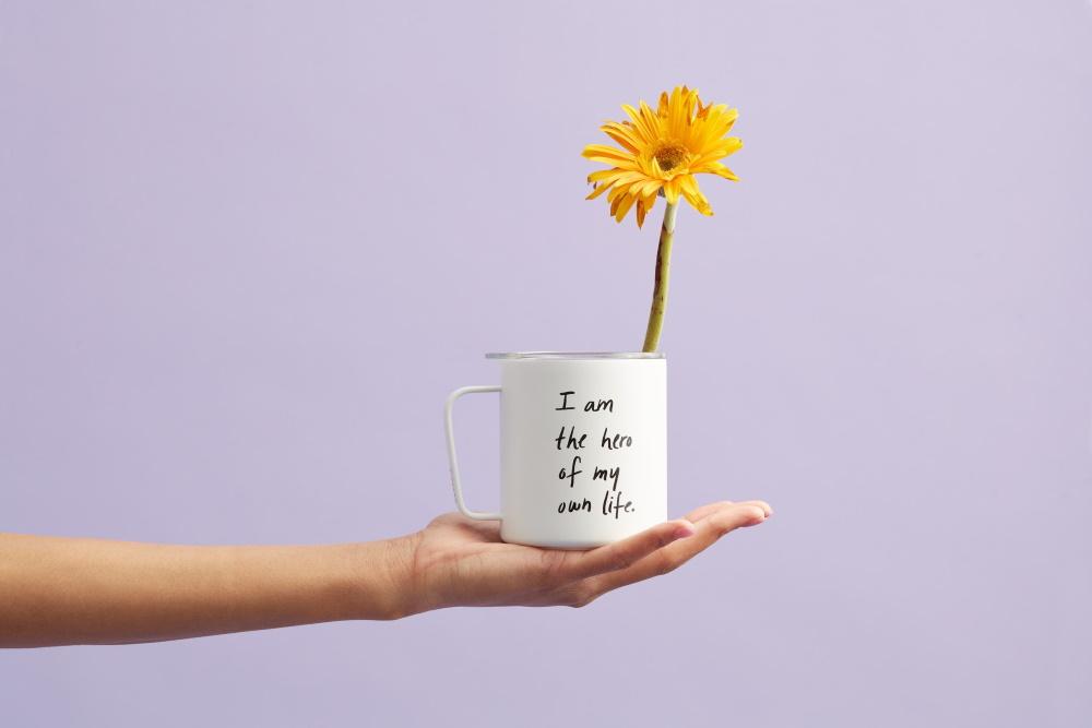 Femeie care tine o cana cu mesaj in engleza, cu o floare galbena