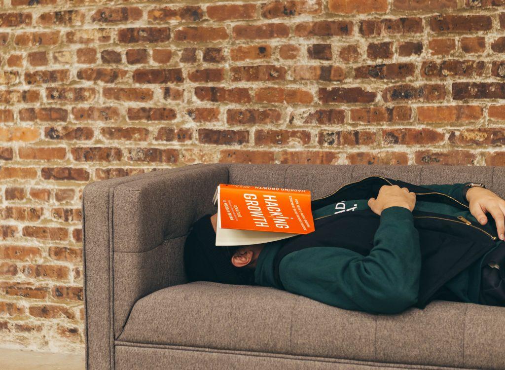 Barbat intins pe o canapea cu o carte pe fata recapituleaza cunostintele la engleza