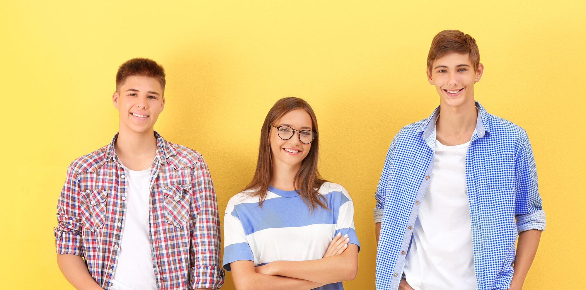 Doi baieti si o fata zambind dupa ce au luat certificatul dupa examenul Cambridge nivel B1 Preliminary