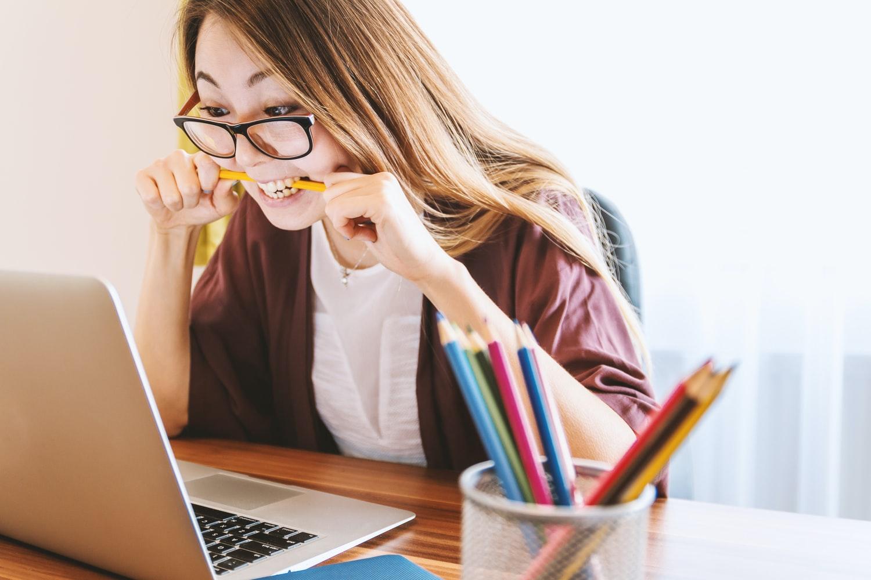 Adult care invata engleza si citeste de pe un laptop care e pe birou