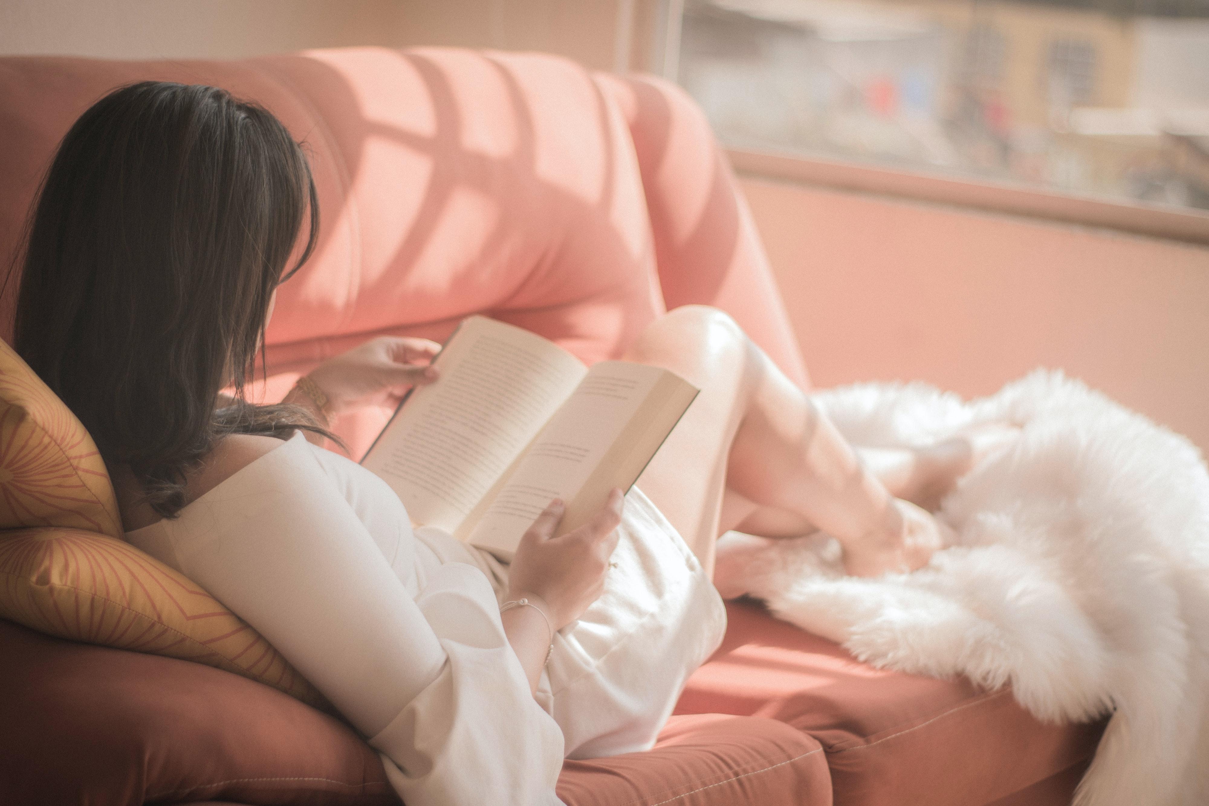 Femeie imbracata asezata confortabil pe canapea citeste o carte in limba engleza