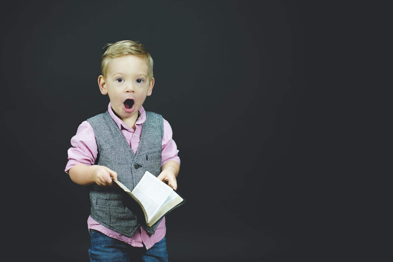 Copil care vorbeste si repeta in limba engleza si tine o carte in mana pe fundal negru