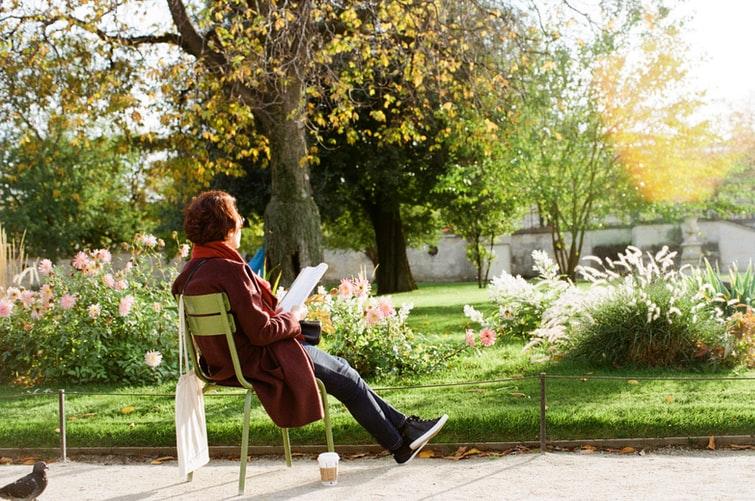 Femeie pe scaun în gradina ei printre flori se relaxeaza si citeste un roman in engleza