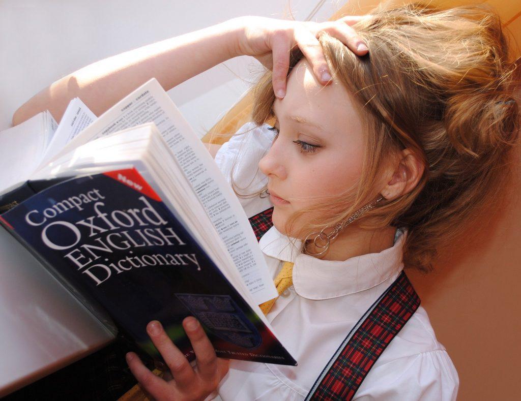 o fata citeste cuvinte noi intr-un dictionar pentru a-si imbunatati nivelul de limba engleza si pentru a putea sustine un examen Cambridge