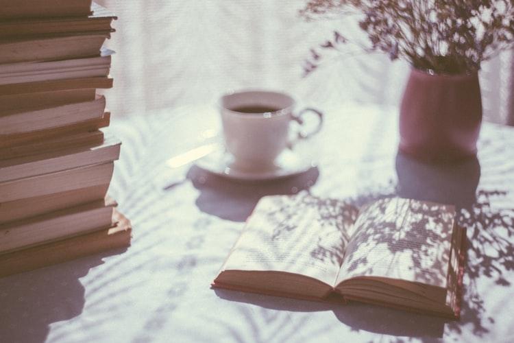 Teanc de carti usor de citit in engleza pe o masa langa o ceasca de cafea si o vaza de flori luminate de razele soarelui