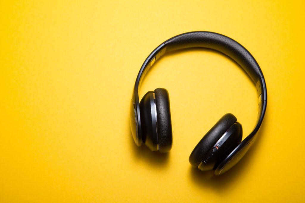 Casti negre pe fundal galben pentru a asculta inregistrari in engleza