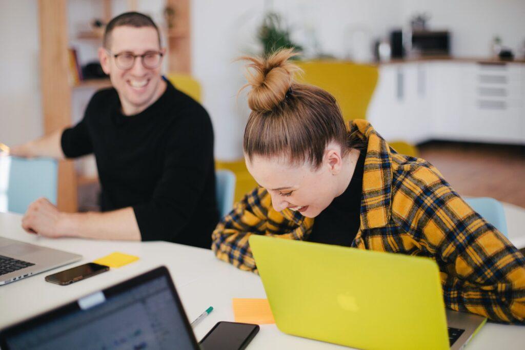 Femeie si barbat in birou lucreaza si glumesc in engleza, nivel avansat, cu laptopurile pe masa