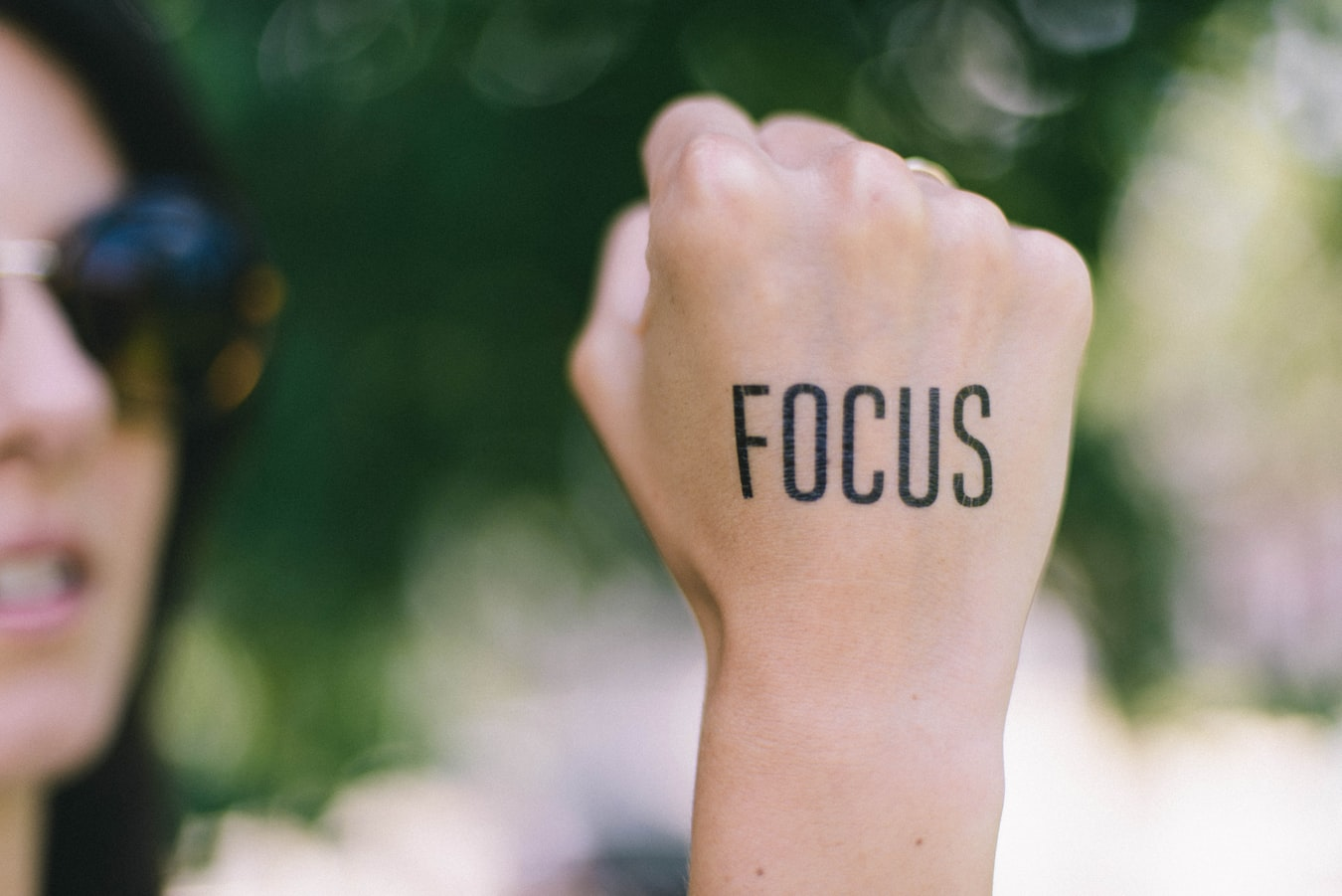 Femeie se concentreaza sa vorbeasca corect engleza avansat in timp ce tine pumnul pe care e scris Focus in aer