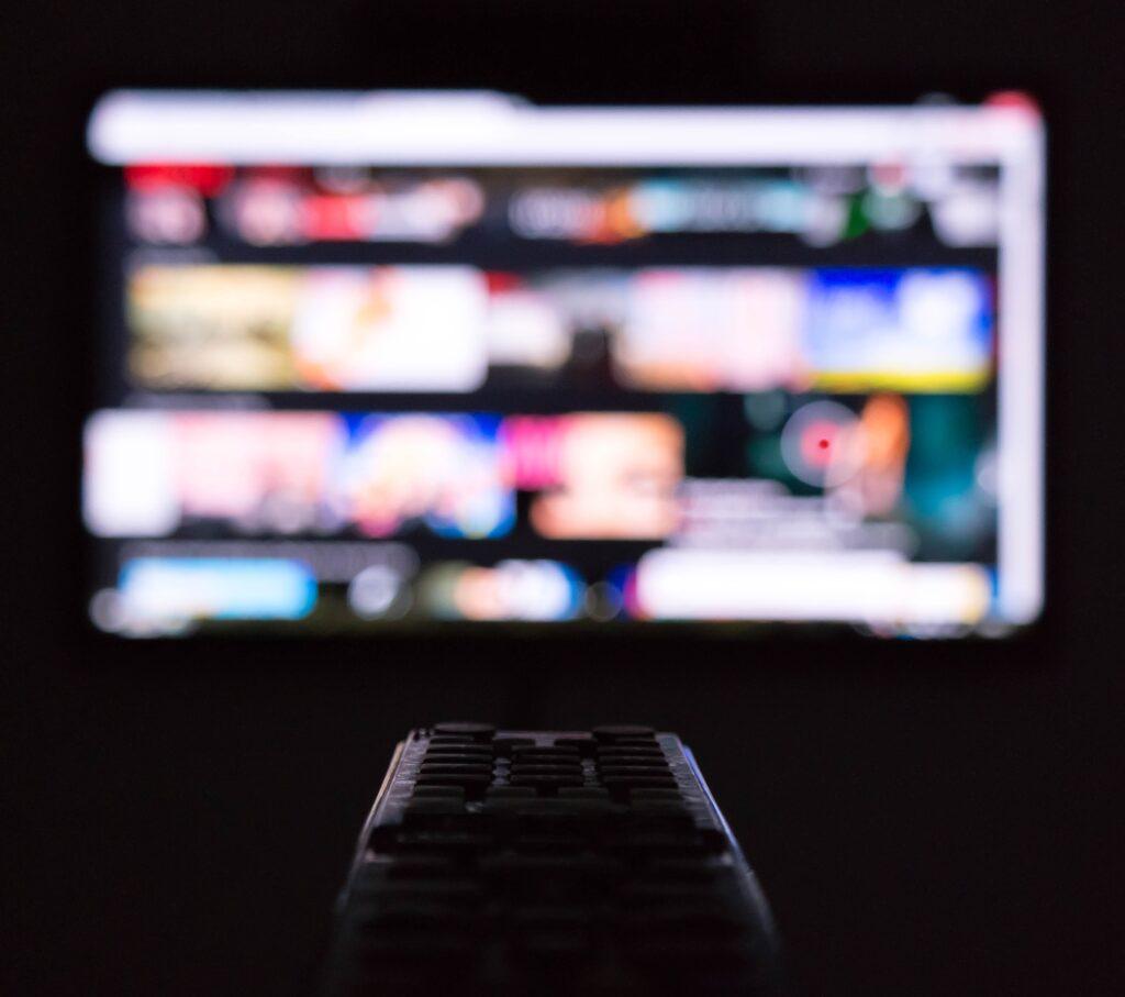 telecomanda indreptata inspre un ecran cu o varietate de filme in limba engleza