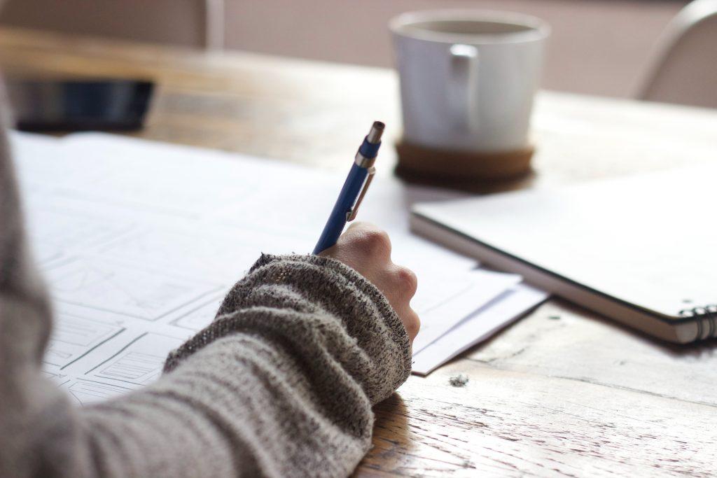 Femeie scrie pe caiet langa alte materiale pentru a invata engleza pe birou