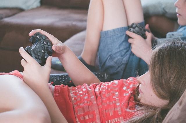 Fata si baiat pe canapea se joaca pe play station