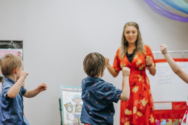 Copii imbracati in albastru in sala de clasa care joaca un joc de miscare alaturi de profesoara lor cu rochie portocalie