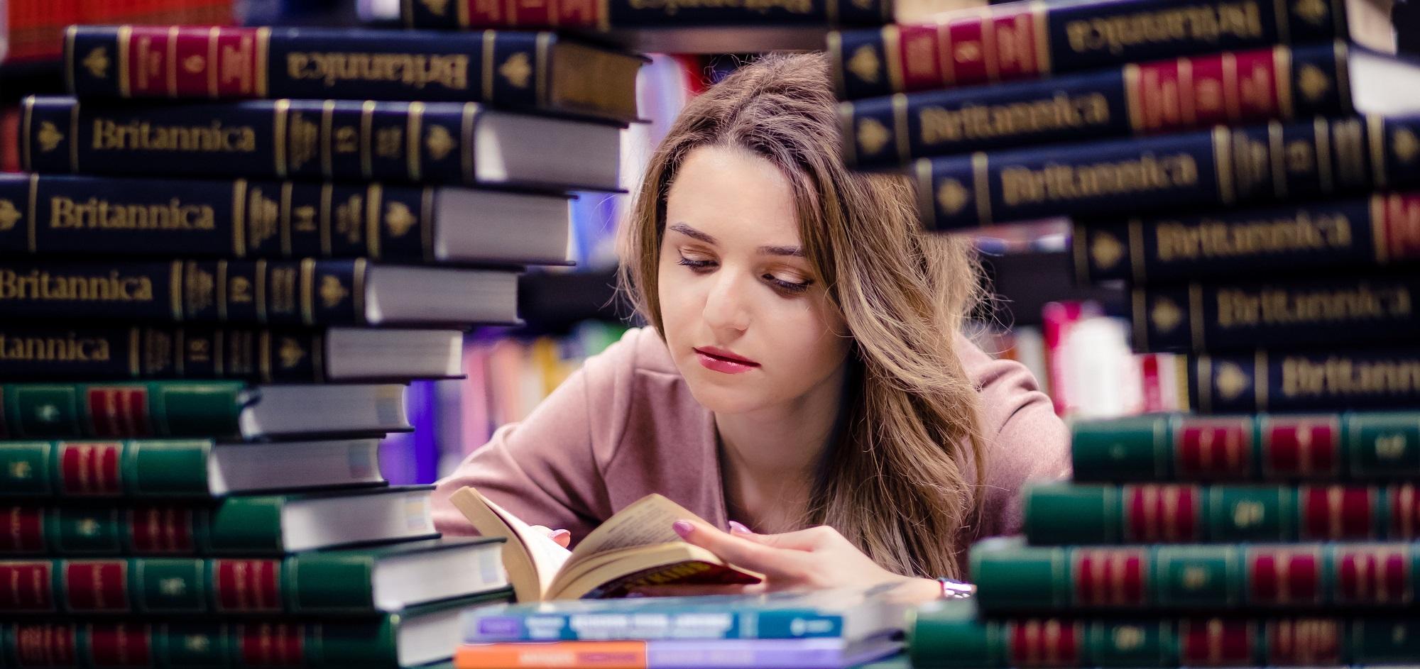 Tanara care citeste printre carti pentru un examen de limba engleza Cambridge CAE sau C1 Advanced