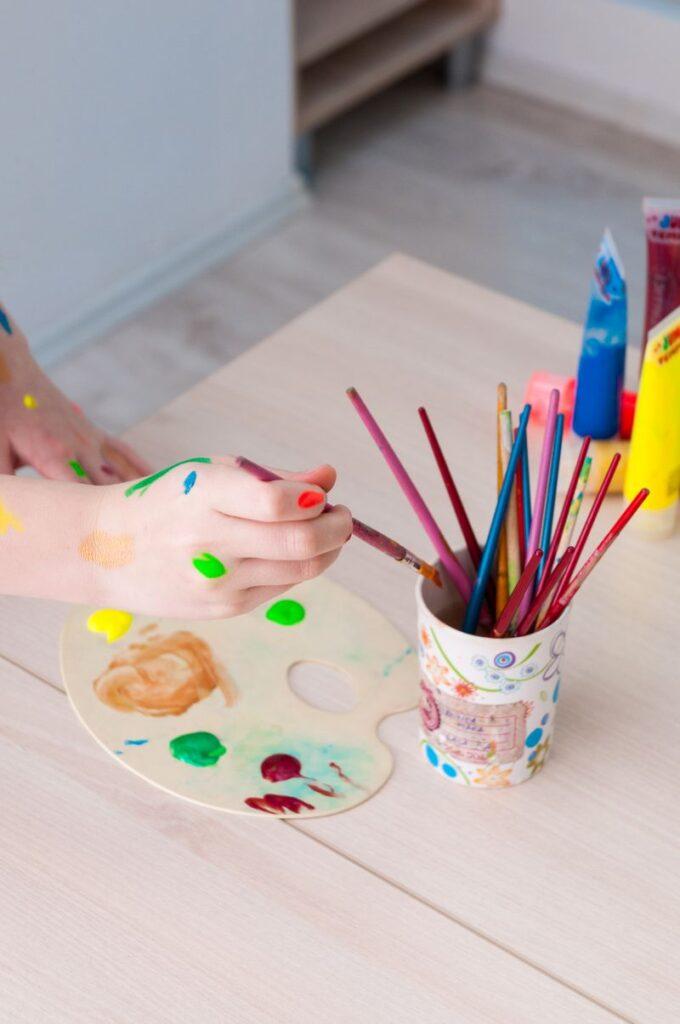 Pahar cu pensule colorate asezat pe masa langa un sevalet cu pete de culoare