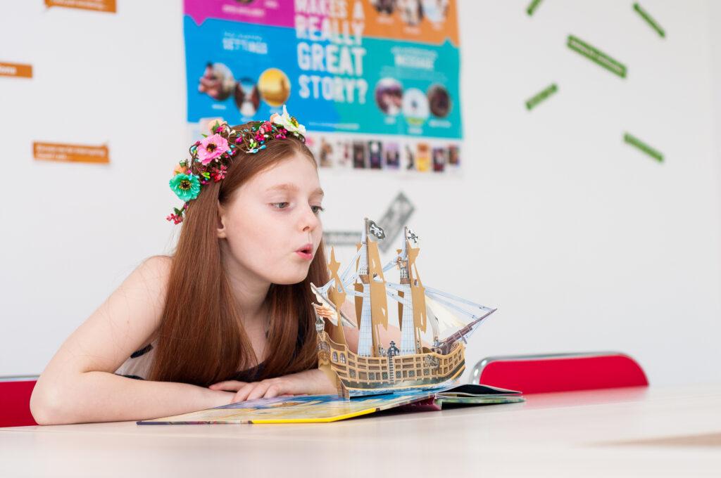 Fetita stand in clasa intr-o banca cu o coronita de flori pe cap rasfoieste o carte de engleza pop-up si sufla intr-o barca