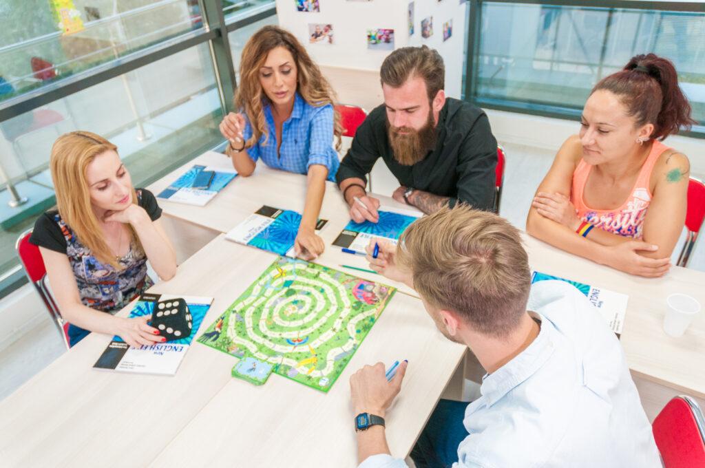 Cursanti tineri in sala de clasa joaca un joc pentru a invata engleza avand in fata manualele pe birou