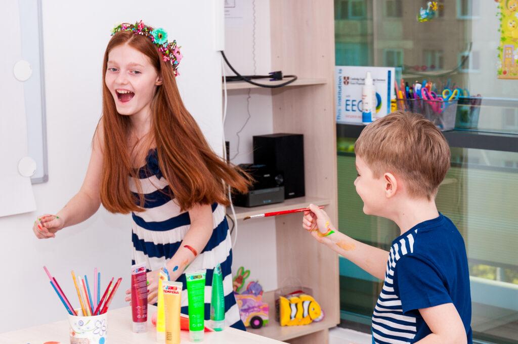 Copii fericiti razand se alearga intr-o clasa si se joaca cu culori pe care le invata in limba engleza