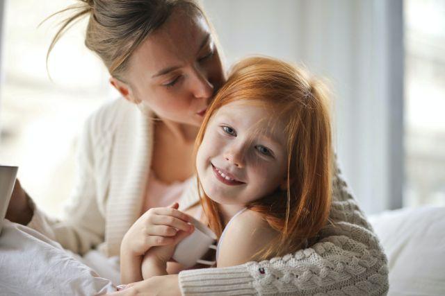 Fetita fericita sta in casa in bratele mamei ei care o pupa si o invata ceva dintr-o carte deschisa