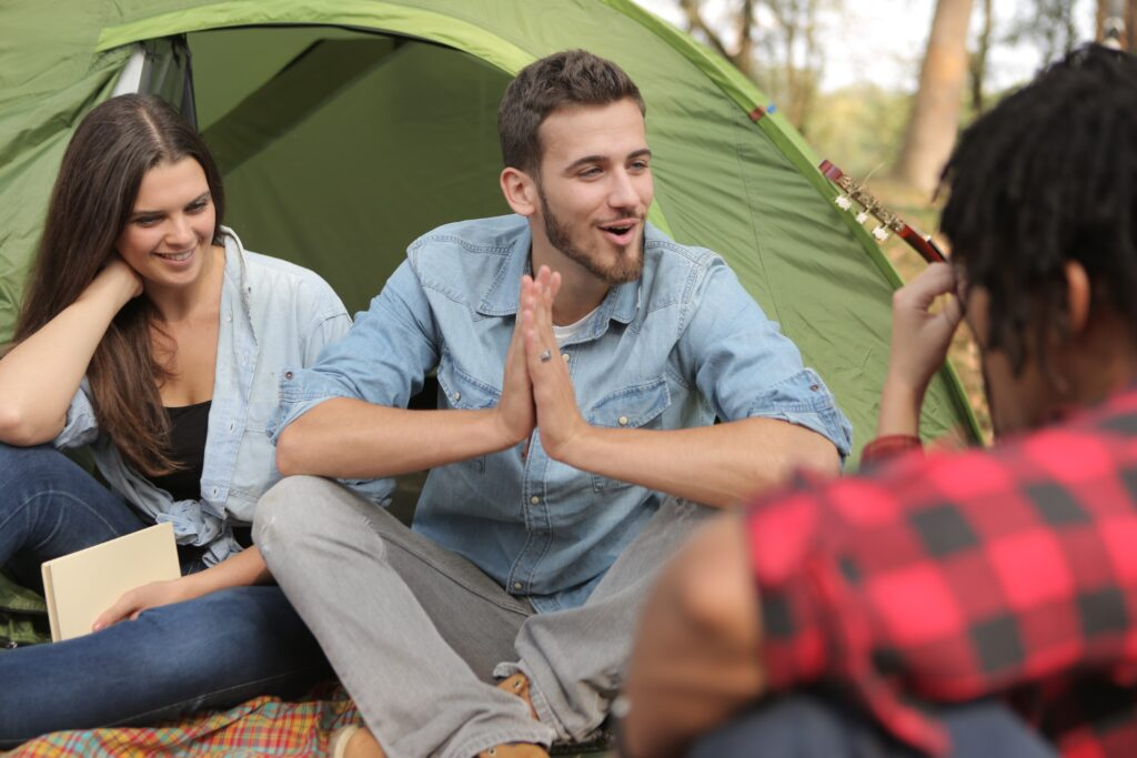 trei tineri in padure in fata cortului vorbesc in engleza nivel avansat si isi povestesc viata