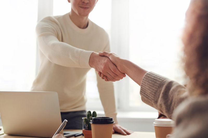 barbat si femeie aflati in birou care fac o intelegere de angajare dand mana peste masa pe care se afla pahare de cafea