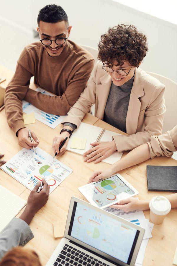 colegi de birou aflati la serviciu discutând grafice colorate legate de investitii si limbile straine necesare pentru comunicarea cu clientii