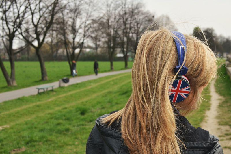 Tânără cu părul lung blond orientată cu spatele se plimbă prin parc ascultând muzică la căşti cu model cu steagul Angliei