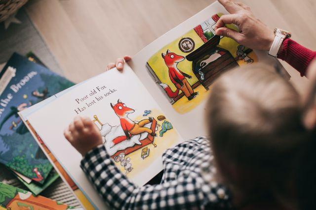 Baietel care citeste o carte ilustrata pentru copii despre o vulpe alaturi de mama lui acasa