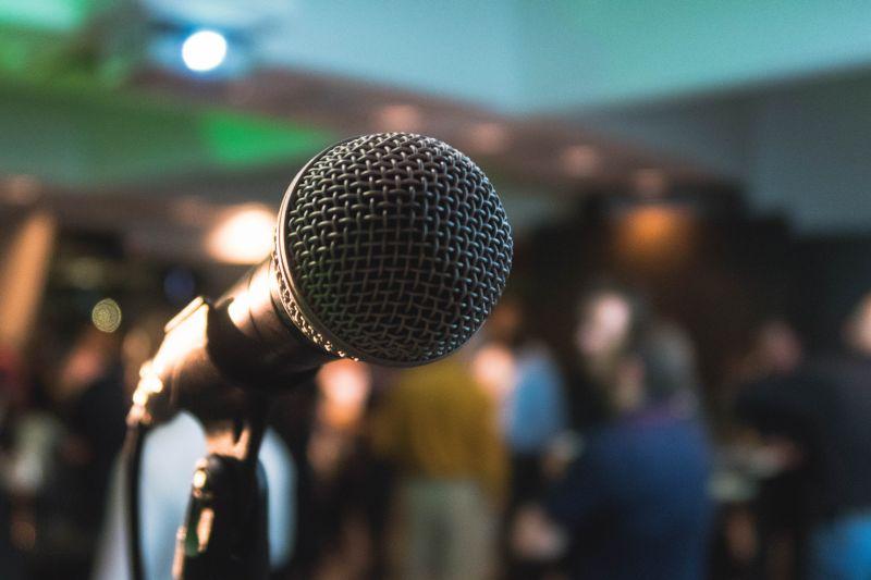 Microfon metalic in prim plan pe fundal de lumini si siluete umane blurate