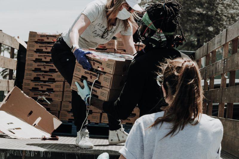 Tineri distribuind cutii cu produse dintr-un camion persoanelor nevoiase
