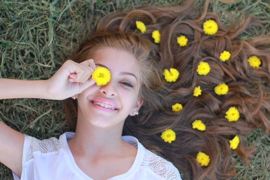 Adolescenta culcata pe iarba cu parul lung si multe papadii in par