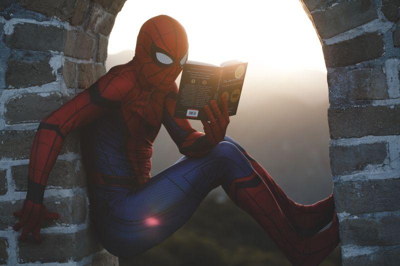 Spiderman asezat in golul de la fereastra unei vechi cladiri citeste o carte avand pe fundal rasaritul soarelui