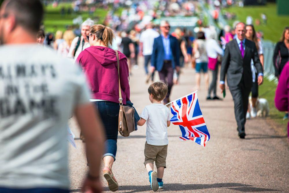 Baietel prescolar care tine in mana dreapta steagul Marii Britanii pentru ca studiaza engleza de mana cu mama lui pe o strada aglomerata din Anglia unde se desfasoara un festival