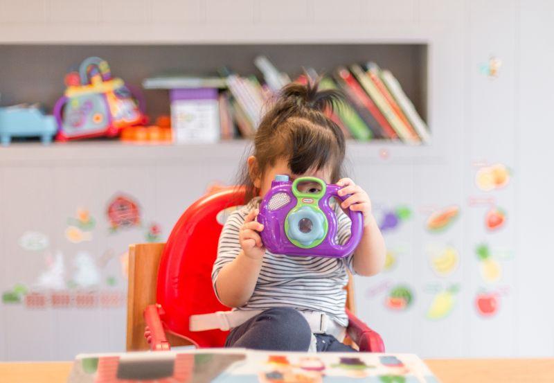 fetita de varsta prescolara asezata pe un scaun rosu de plastic la masa intr-o camera cu multe jucarii se joaca si se preface ca fotografiaza pe cineva in cadrul unui joc de invatare a limbii engleze