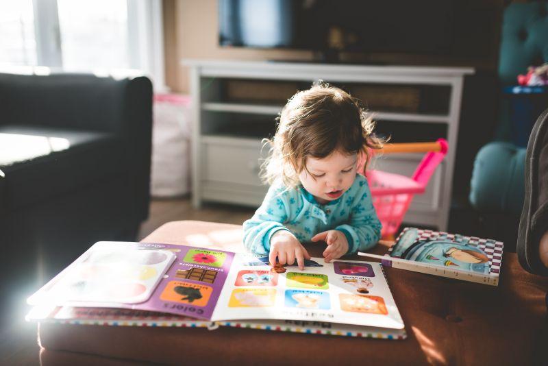 fetita de varsta prescolara rasfoieste o carte cu poze si numeste diferite obiecte cu voce tare pentru a invata engleza