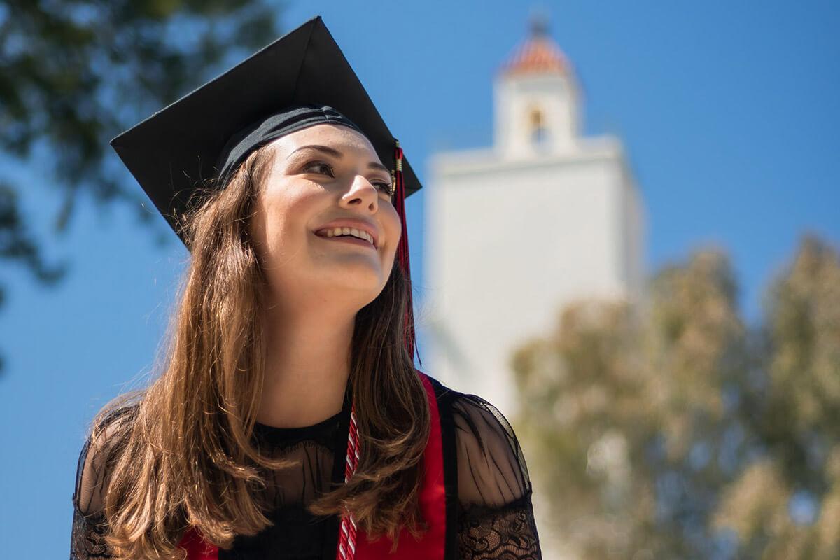 adolescenta imbracata in haine festive si cu palarie de absolvent, fericita ca a sustinut si promovat examenul Cambridge, avand pe fundal cladirea unei universitati din Anglia