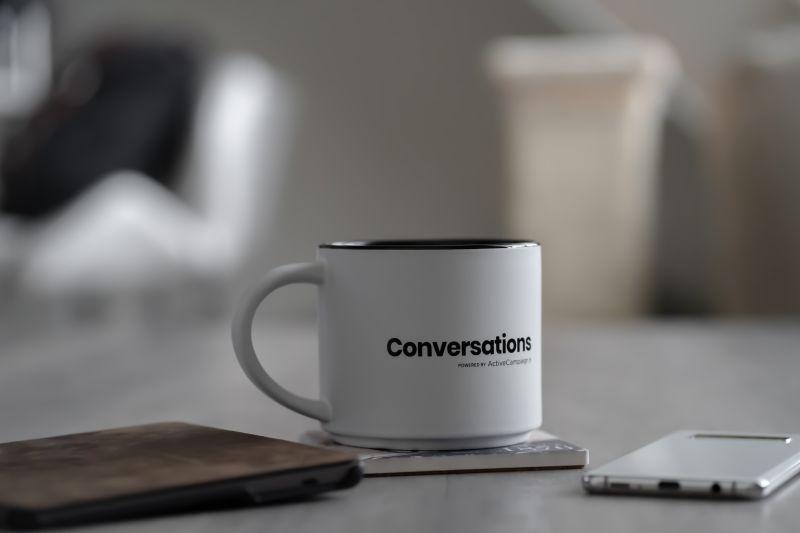 Cana alba de cafea in prim plan pe care scrie Conversations cu negru pe un birou alaturi de un telefon si un carnetel