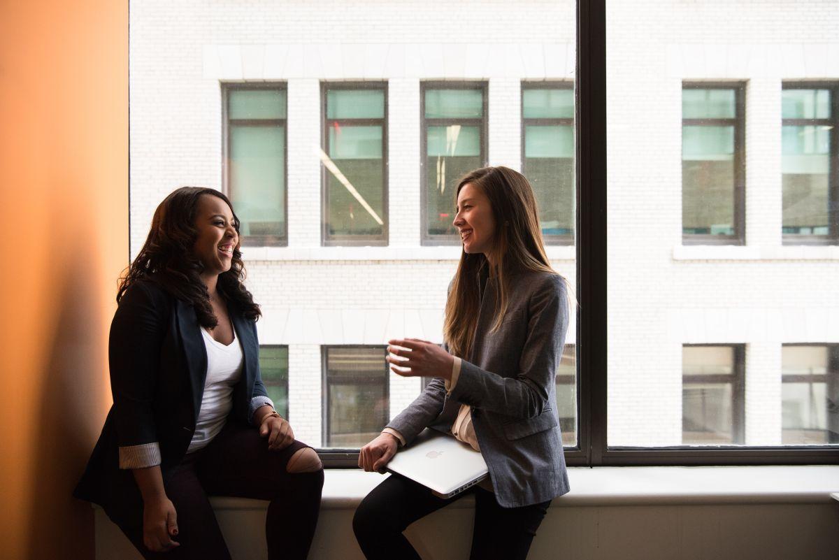 Femei tinere imbracate smart casual stau pe pervazul unei ferestre a unei clădiri de birouri si au o conversatie fluenta in engleza care le face sa zambeasca