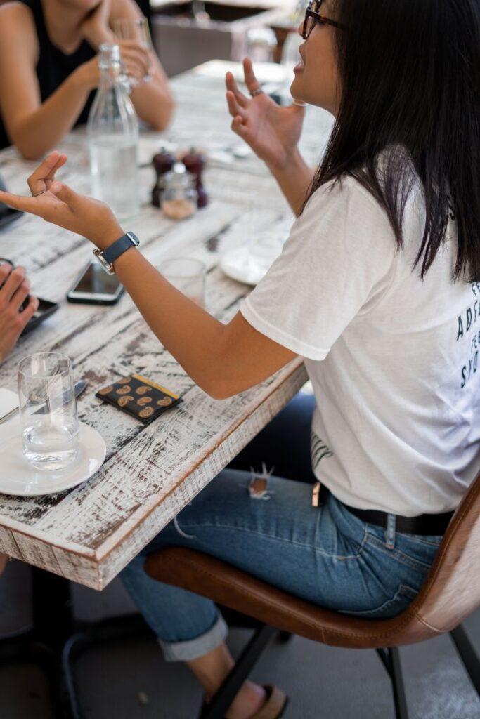 Tânără îmbrăcată casual la o masă la restaurant care conversează în engleză cu prietenele ei gesticulând foarte mult