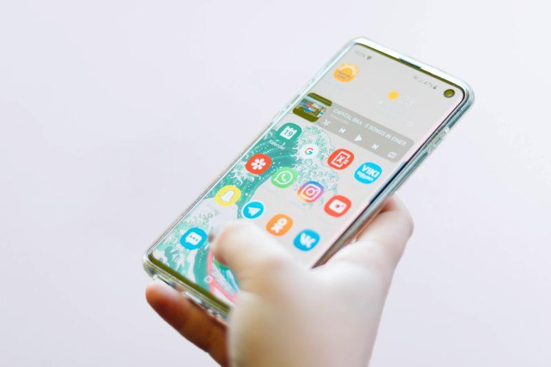 Mana tinand un smartphone cu ecranul deschis, cu diverse aplicatii si cu degetul mare apasand pe un icon care deschide o platforma digitala