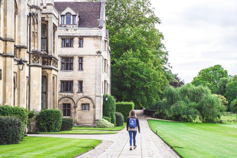 Privire de ansamblu asupra fatadei unui corp de cladire a Universitatii Cambridge, a aleii pe care trece un student si a peluzei din fata ei