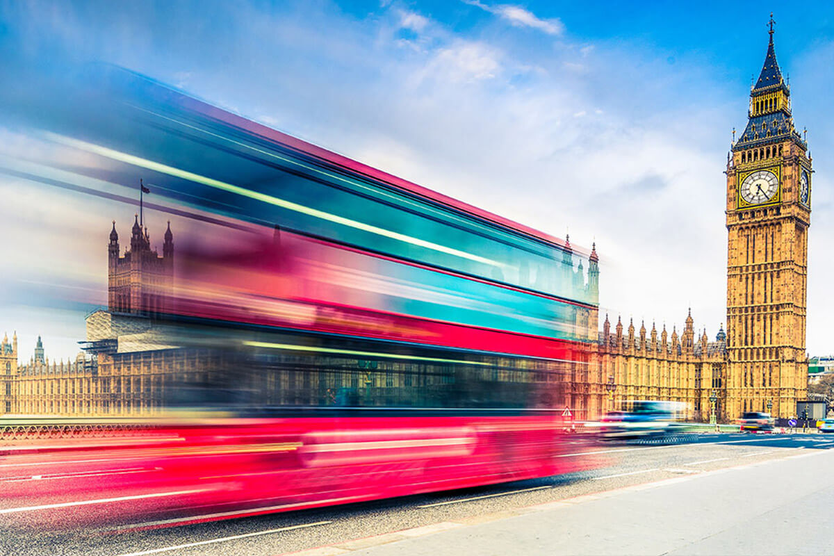Autocar double decker rosu cu albastru care trece cu viteza foarte mare pe langa Big Ben