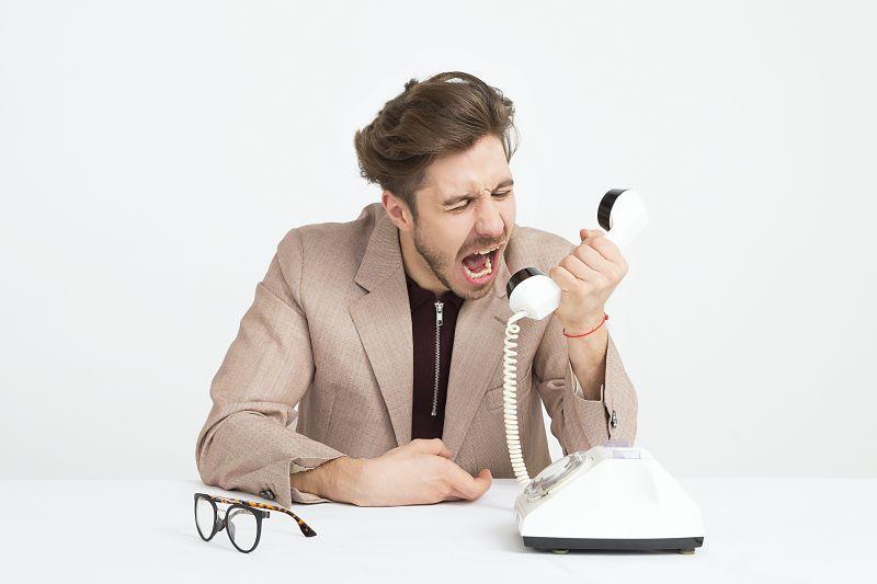 Tanar saten imbracat in sacou bej care telefoneaza unui prieten de pe un telefon fix alb si tipa dupa ajutor pentru ca nu reuseste sa invete usor