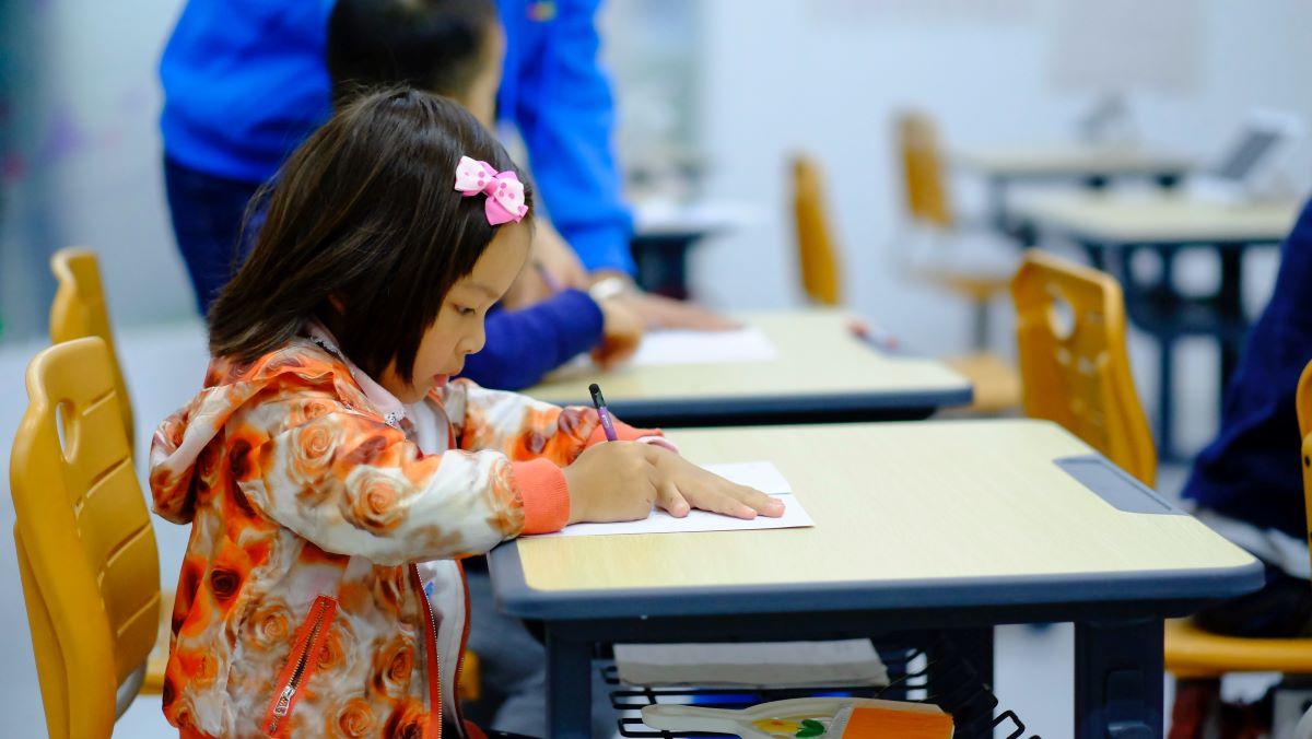 fetita de 7 ani sta pe scaun galben la birou in clasa la cursul de engleza si scrie pe caiet