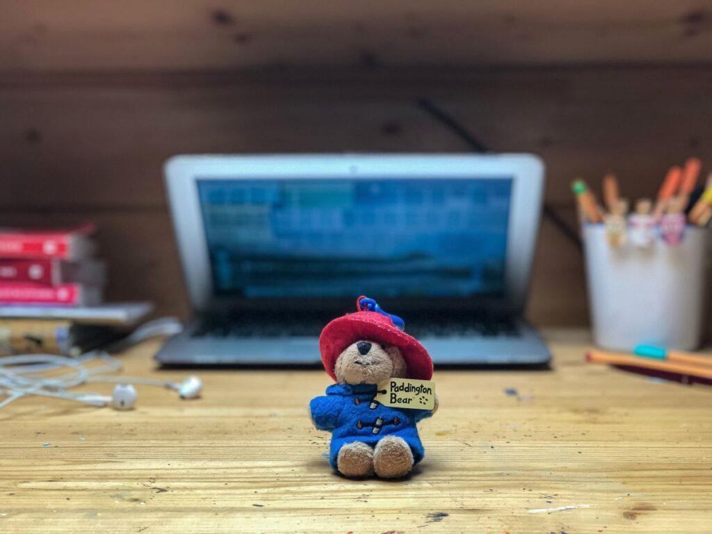 birou de lemn natur pe care se afla un laptop deschis, un teanc de carti, un pahar cu creioane si pixuri blurate si o figurina ursulet Paddington in prim-plan