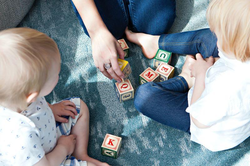 Copii prescolari se joaca pe podea cu profesoara lor la cursul de engleza cu niste cuburi de lemn cu litere si invata sa citeasca si sa scrie