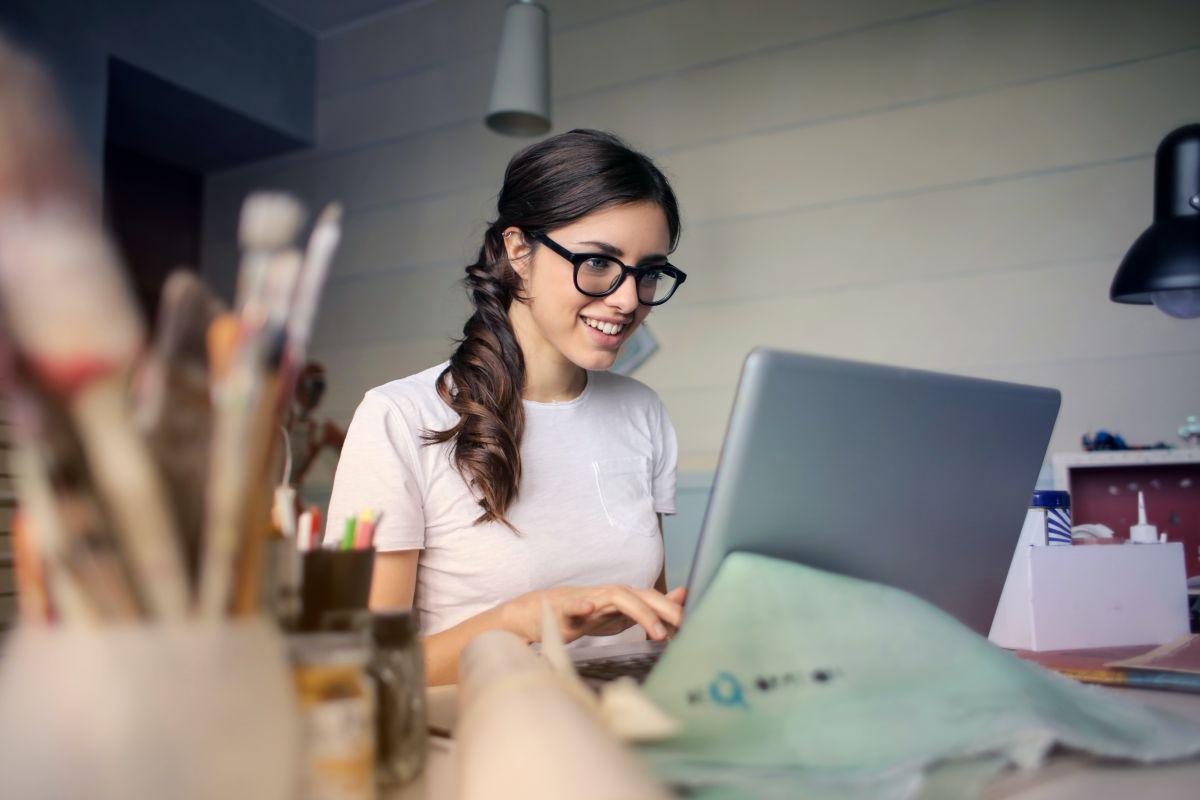 Femeie tanara cu parul prins in coada si ochelari care sta in fata laptopului si zambeste la colegii ei de la cursul de engleza online avand un borcan de creioane in prim plan